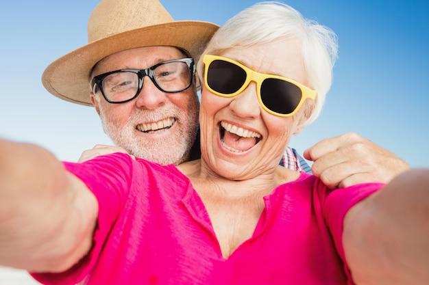 Ältere paare, die selfie mit smartphone nehmen