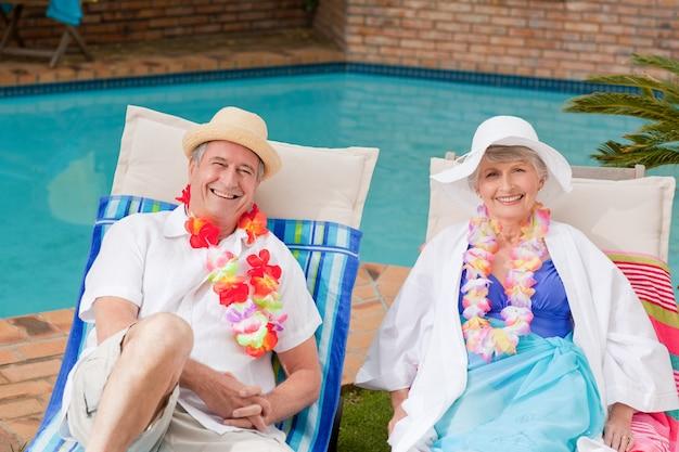 Ältere paare, die sich neben dem swimmingpool hinlegen