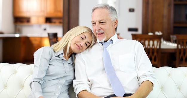 Ältere paare, die sich zu hause auf sofa entspannen