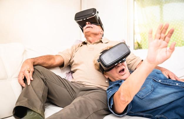 Ältere paare, die spaß zusammen mit kopfhörer der virtuellen realität haben