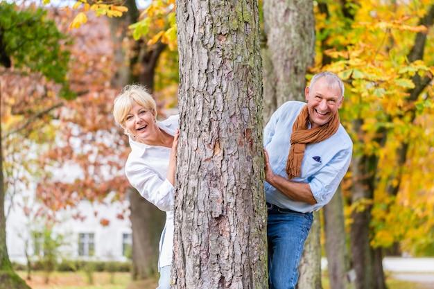Ältere paare, die um baum im park flirtend spielen