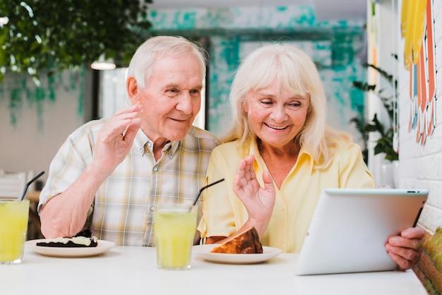Ältere paare, die videoanruf auf tablette haben