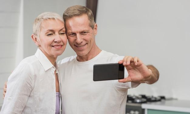 Ältere paare, die zu hause ein selfie nehmen