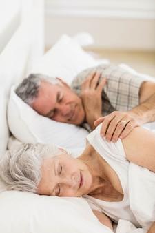 Ältere paare, die zu hause im bett schlafen