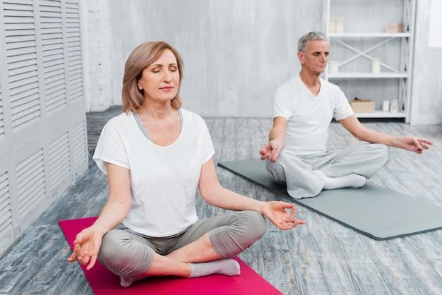 Ältere paare, die zu hause meditation auf übungsmatte durchführen