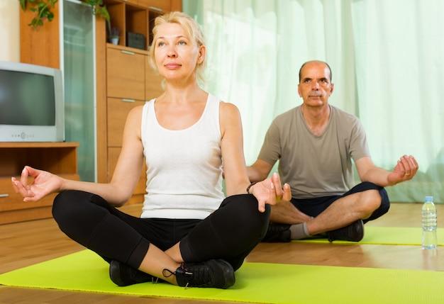 Ältere paare, die zu hause yoga haben