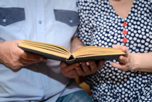 Ältere paare, die zusammen eine nahaufnahme des buches lesen