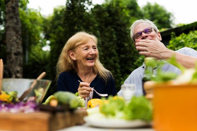 Ältere paare, die zusammen frischgemüsesalat am hinterhof essen