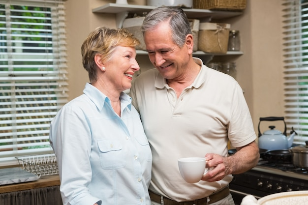 Ältere paare, die zusammen kaffee zu hause in der küche trinken