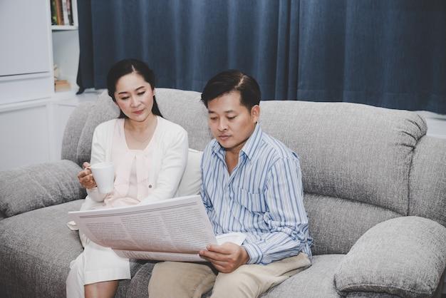 Ältere paare eine mannlesezeitung mit einer frau, die den tasse kaffee zusammen sitzt auf sofa im wohnzimmer hält