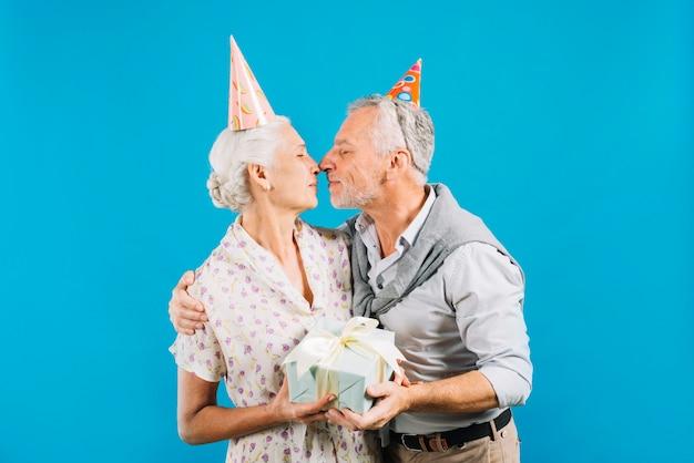 Ältere paare mit dem geburtstagsgeschenk, das auf blauem hintergrund sich liebt