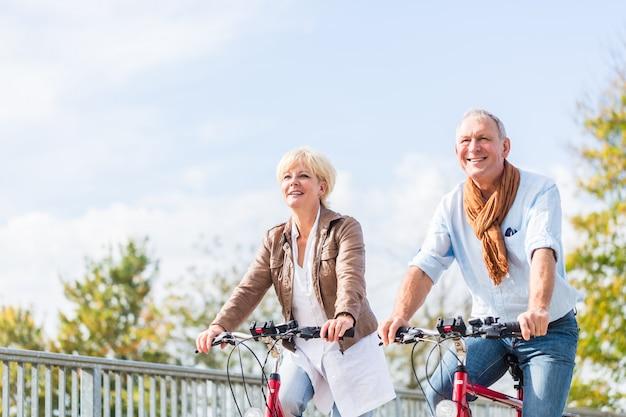 Ältere paare mit fahrrädern auf brücke