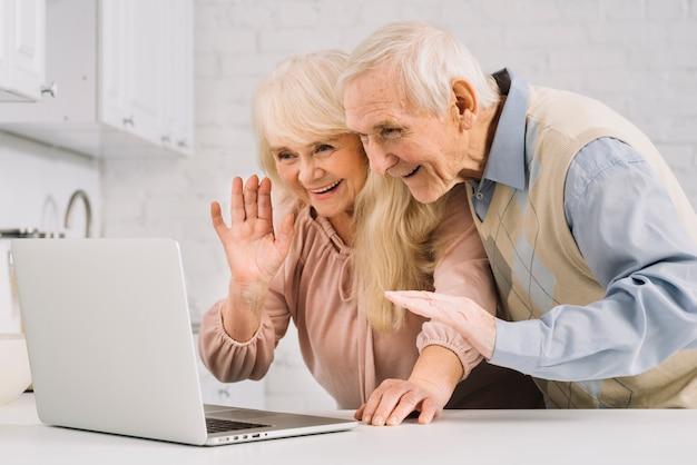 Ältere paare mit laptop in der küche