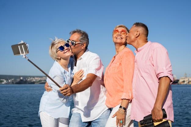 Ältere paare mit mittlerem schuss, die selfie nehmen