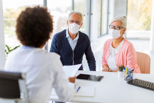 Ältere paare mit schützenden gesichtsmasken erhalten nachrichten von einer schwarzen ärztin im büro