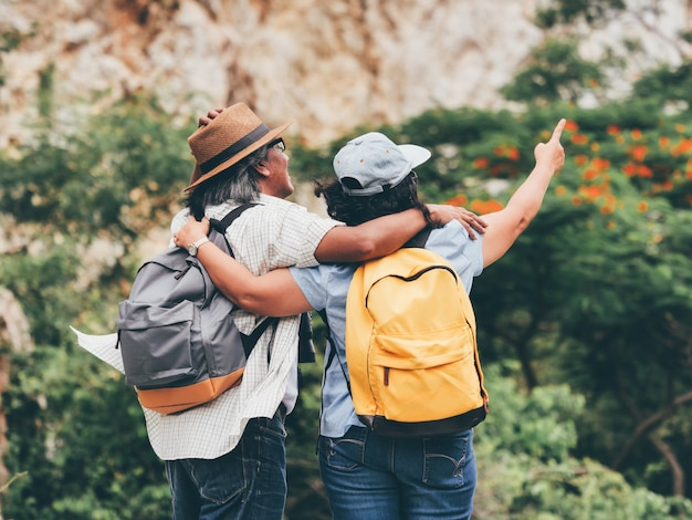 Ältere paare reisen auf sommerferien. sie halten händchen und wandern zusammen.
