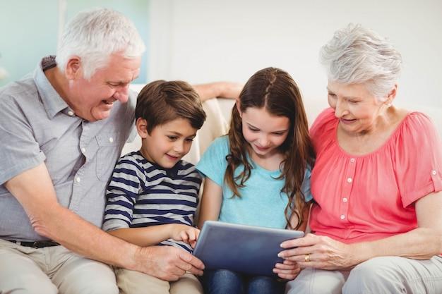 Ältere paare und ihre großartigen kinder, die digitale tablette im wohnzimmer verwenden