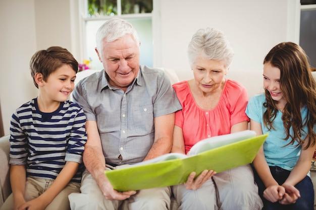 Ältere paare und ihre großartigen kinder, die ein buch im wohnzimmer lesen