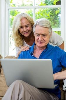 Ältere paare unter verwendung des laptops beim an zu hause sitzen