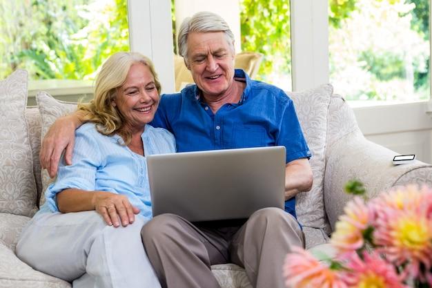 Ältere paare unter verwendung des laptops beim sitzen auf sofa