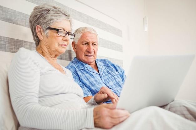 Ältere paare unter verwendung des laptops im schlafzimmer