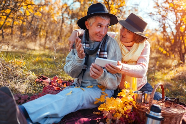 Ältere paare unter verwendung des telefons beim trinken des tees und unterhaltung im herbstwald