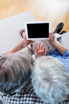 Ältere paare unter verwendung einer digitalen tablette auf sofa