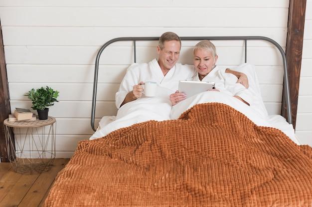 Ältere paare unter verwendung einer tablette im bett