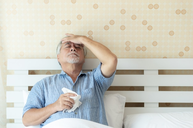 Ältere patienten im bett, asiatische ältere mannpatienten-kopfschmerzenhände auf stirn