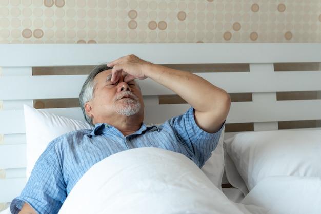 Ältere patienten im bett, asiatische kopfschmerzenhände des älteren mannes auf stirn.