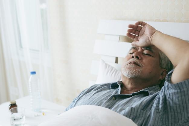 Ältere patienten im bett, medizinisches und gesundheitswesenkonzept des asiatischen patienten des älteren mannes kopfschmerzen