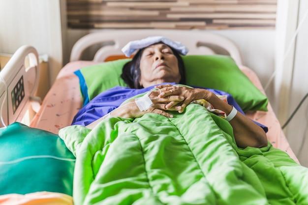 Ältere patientenhand mit injektionssalzlösung, die im krankenhausbett liegt