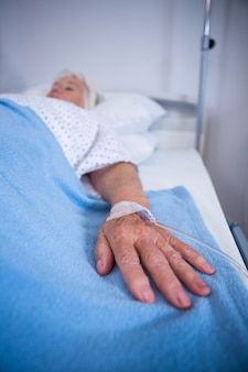 Ältere patientenhand mit kochsalzlösung auf bett im krankenhaus