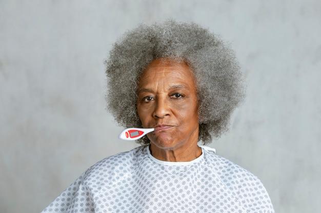 Ältere patientin, die ihre temperatur überprüft