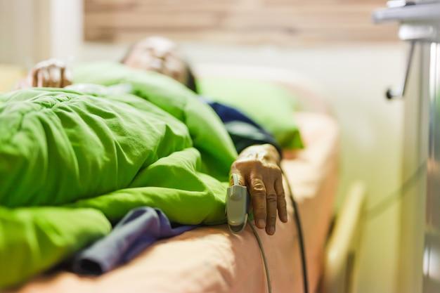 Ältere patientin im bett liegend mit fingerspitzen-pulsoximeter