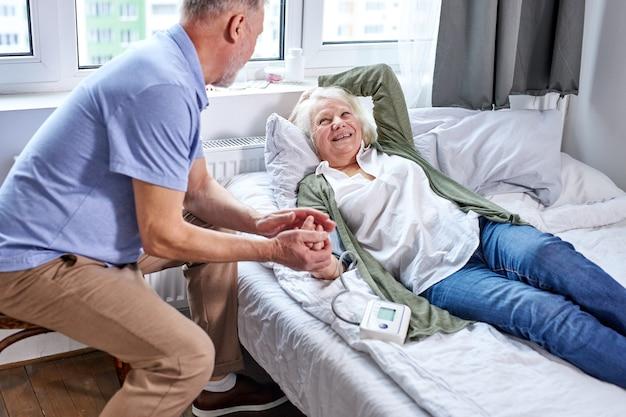Ältere patientin im krankenhaus mit besorgtem ehemann, der hände hält, während blutdruck mit tonometer prüft. mann hilft, unterstützt