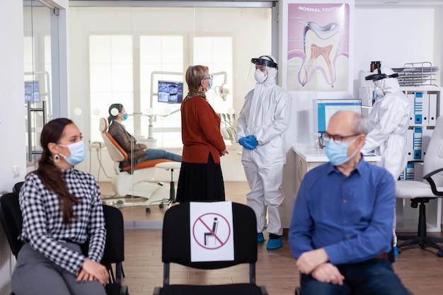Ältere patientin in der stomatologie-klinik, die mit einem arzt in ps-anzug als sicherheitsvorkehrung während der globalen pandemie mit coronavirus diskutiert