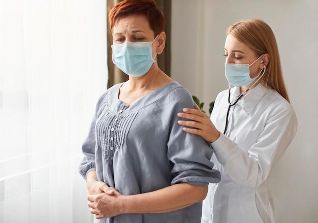 Ältere patientin mit medizinischer maske und ärztin des covid recovery center mit stethoskop
