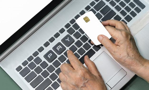 Ältere person, die kreditkarte für online-einkäufe verwendet