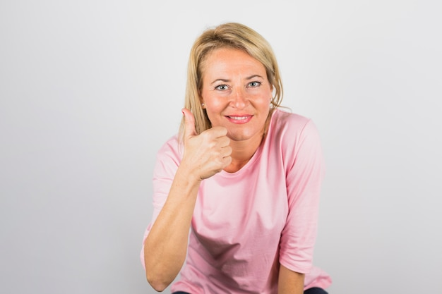 Ältere positive frau in der rosafarbenen bluse mit dem daumen oben