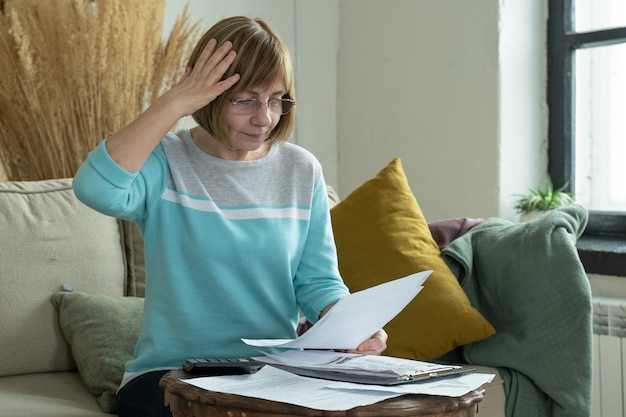 Ältere reife frau unter verwendung des rechners, der papierrechnung hält, die geldbudgetsteuer berechnet
