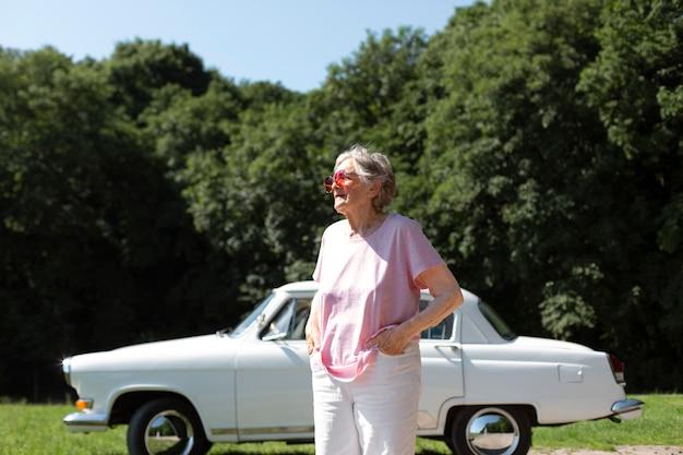 Ältere reisende mit roter sonnenbrille neben ihrem auto her