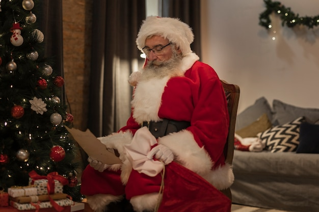 Ältere sankt, die einen weihnachtsbrief liest