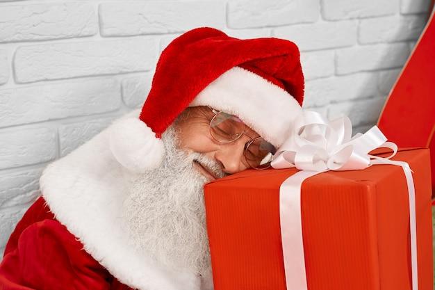 Ältere santa claus, die auf roter geschenkbox im weißen studio schläft