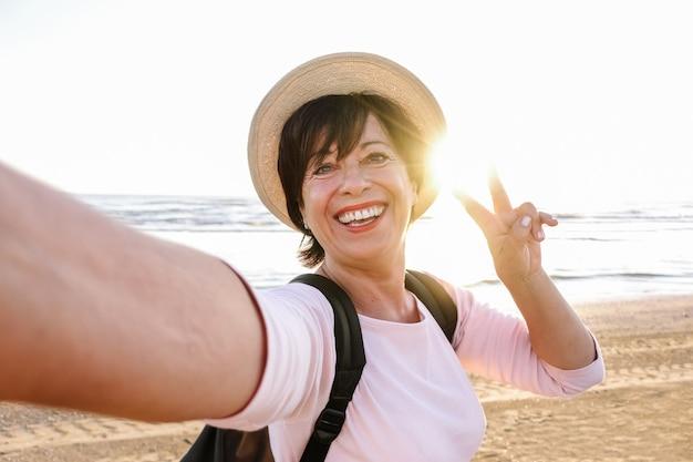 Ältere schöne frau mit hut und rucksack lächelnd und ein selfie am strand nehmend