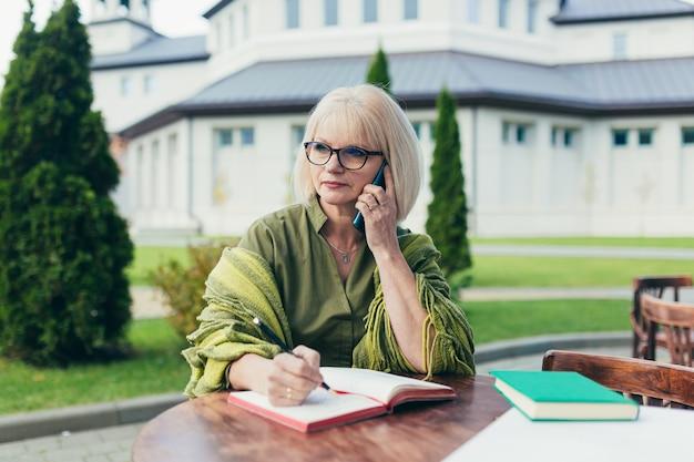 Ältere schöne geschäftsfrau, die auf einem stuhl sitzt und notizen in einem notizbuch macht, mit einem telefon und laptop im hof