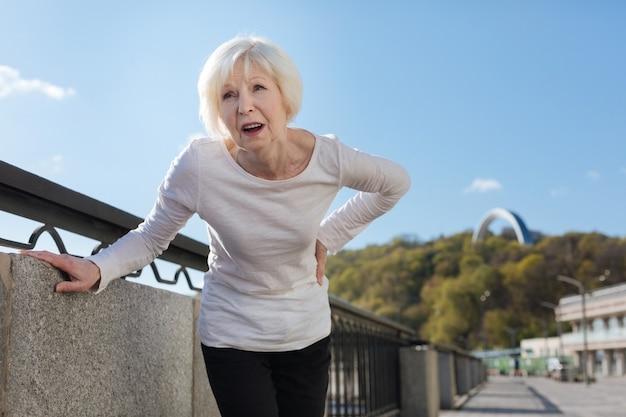 Ältere schöne stilvolle dame, die plötzlich verletzt wird und ihren rücken berührt, während sie herumläuft