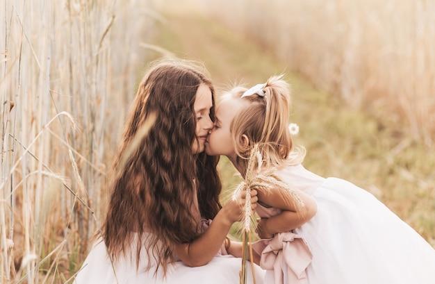 Ältere schwester küsst im sommer in der natur die wange der jüngeren. kinder umarmen.