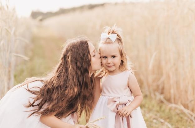 Ältere schwester küsst im sommer in der natur die wange der jüngeren. kinder umarmen. Premium Fotos