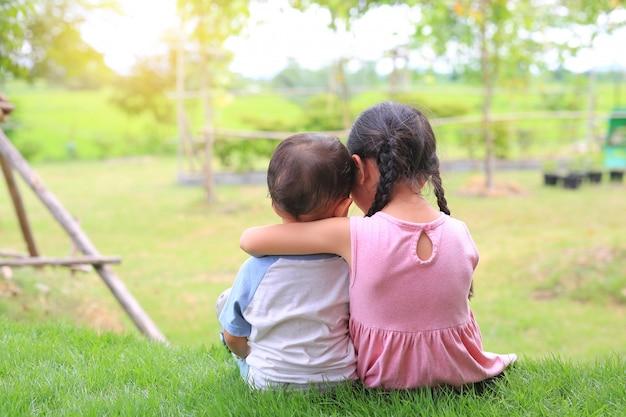Ältere schwester umarmt kleinen bruder am hals, schultern sitzen auf der grünen wiese. zwei entzückende asiatische kinder, welche die hintere ansicht des stutzens sitzen und umarmen.